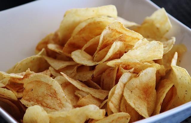 Hauchdünn geschnittene Kartoffelchips in einer Schüssel präsentiert.